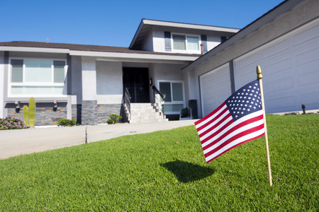 A homeowner displays an American flag in their yard during a patriotic holiday