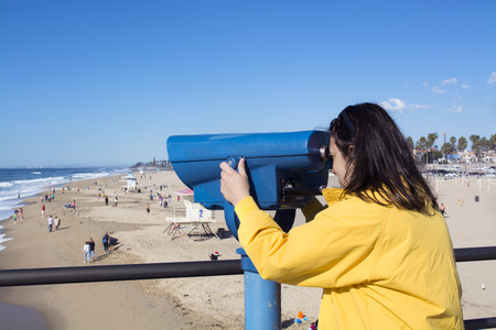 A tourist on the Huntington Beach pier watches surfers through coin operated binoculars during a bright, sunny day. photo