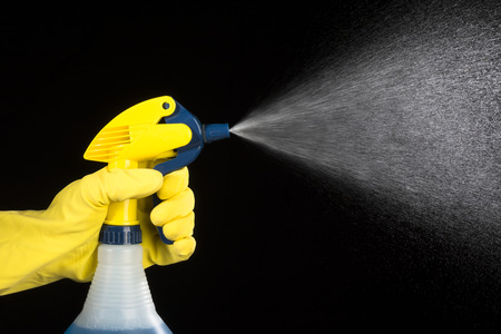 A person uses a hand held pump sprayer and protective glove to spray cleaning chemicals.