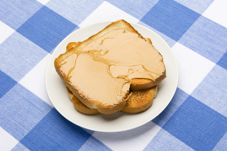 checker plate: Fresh, hot breakfast toast spread with peanut butter to be consumed during mealtime.