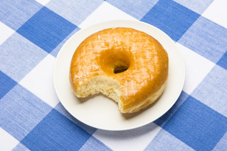 checker plate: Delicious glazed donut with bite taken out during breakfast