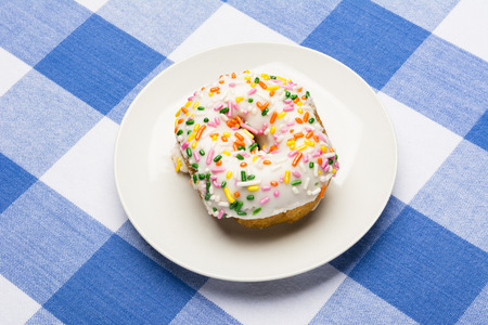 checker plate: A fresh, delicious icing coated cake donut with sweet sprinkles on a classic, checkered diner tablecloth