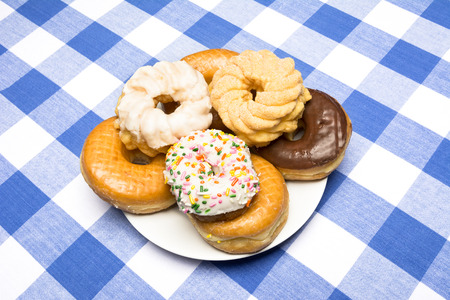 checker plate: A plate of delicious, fresh donuts on a classic diner checkered blue and white tablecloth Stock Photo