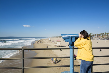 A tourist on the Huntington Beach pier watches surfers through coin operated binoculars during a bright, sunny day. T photo