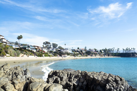 cove: A view of a secluded beachfront cove shows beautiful turquoise water hugging the sandy shore in Laguna Beach, California