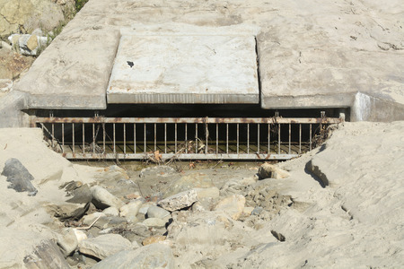 runoff: A beach sewer used to drain water runoff from the cliff side during heavy rains to control flooding Stock Photo