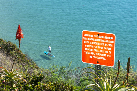 posted: A sign posted on the side of a cliff warning hikers to keep a safe distance from the edge. Stock Photo