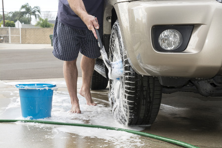 A man washing his car uses a soapy brush to clean the tires and wheels of his vehicle. photo