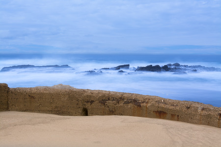 seawall: A seawall separates the rough ocean from a sandy beach during an early morning sunrise Stock Photo