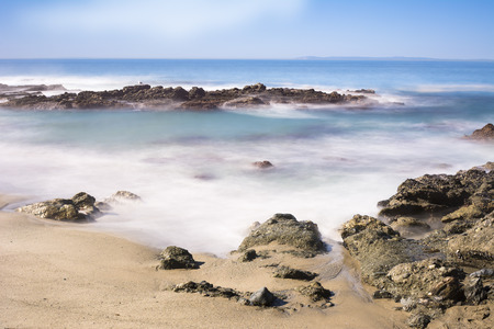 seawater: Slow motion scenic of a beautiful reef with seawater rushing over a rugged shoreline reef in Laguna Beach, California.