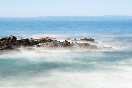 slow motion: Slow motion scenic of a beautiful reef with seawater rushing over a rugged offshore reef in Laguna Beach, California.