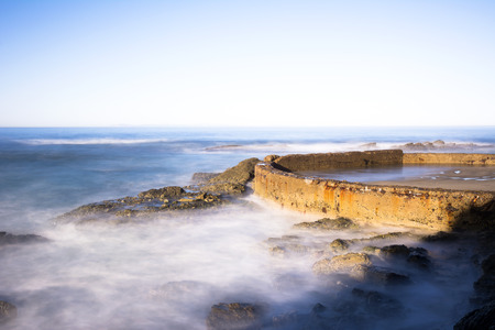 seawall: A sea wall lit by a morning sunrise protects a small, enclosed sandy beach from oncoming waves as they crash and splash high into the air. Stock Photo
