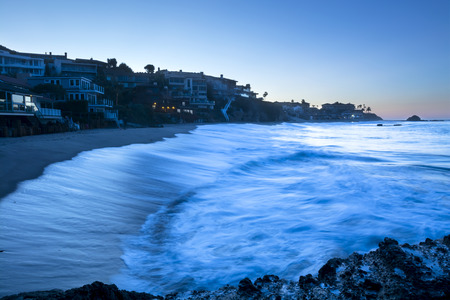rushes: A wave lit by the bright moonlight rushes to the shore of a sandy cove with affluent homes. Stock Photo
