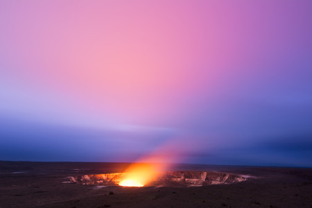 kilauea: A long exposure during the early evening shows the glowing lava lake in the caldera of Hawaiis Kilauea Volcano as it bounces light off of the haze drifting by in the sky. Stock Photo