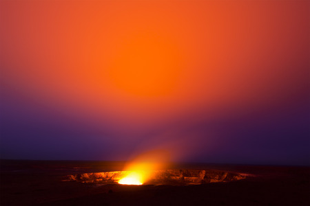 caldera: A 30-minute exposure at 3am of the glowing lava lake in the caldera of Hawaiis Kilauea Volcano bounces light off of the haze drifting by in the sky.