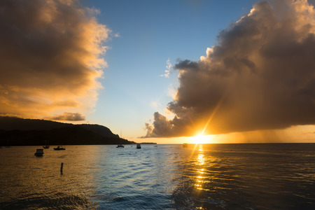 storm clouds: A Hawaiian sunset just after a storm shows the dark clouds still lingering over the calm Hanalei Bay.