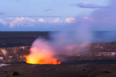 spewing: As the sun sets Kilauea volcano begins to show the hot lava glow of its active vent, spewing out smoke as the molten rock burns. Stock Photo