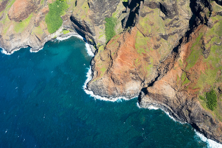 na: An aerial view of the Na Pali coast in Kauai Hawaii during a vibrant, sunny day shows the rich colors of the scenic coastline.N