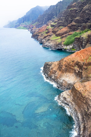 hawaii islands: An aerial view of the Na Pali coast in Kauai Hawaii during a vibrant, sunny day shows the rich colors of the scenic coastline. Stock Photo