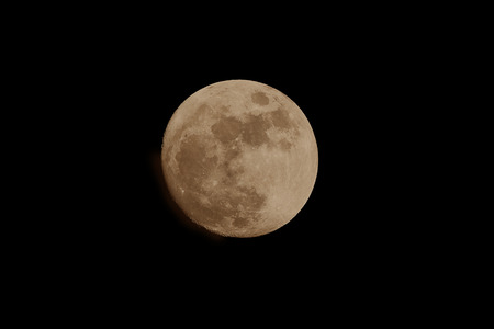 Image of a full amber moon shot during the evening shows orange color the planet casts at certains times of the year.