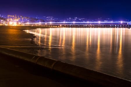 santa barbara: Image of a long exposure in Santa Barbara Harbor California during nighttime with famous Stearns Wharf lining the horizon