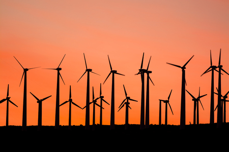 Renewable energy windmills line the mountaintops of Palm Springs at sunset