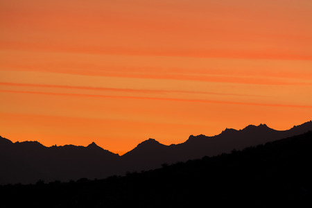 A dramatic sunset in the hills of Palm Springs shows beautiful striations in a deep orange sky