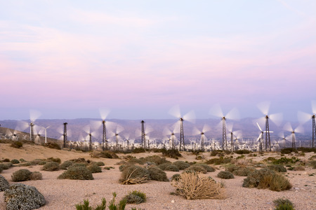 windmills: Renewable energy windmills line the mountaintops of Palm Springs during sunset