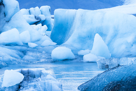 Icebergs along the shore of Jokulsarlon glacial lagoon during a blue overcast day rest motionless while framed by cold ocean water. Imagens - 70656021