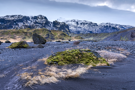 unaffected:   Wilderness mountain countryside in Iceland during a stormy afternoon shows the barren look of a volcanic landscape and dry vegetation.