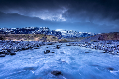 A river formed by melting glaciers flows through a mountain range in northern Iceland during a dark, rainy day.
