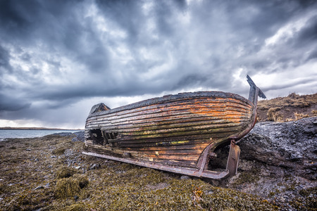 An old abandoned fishing vessel from the early 1900s rests on a remote beach as it rots, exposing the ships wooden ribs and hull infrastructure.