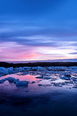 Icebergs in Jokulsarlon glacial lagoon during a vibrant red sunrise rests motionless as it is framed by cold ocean water.