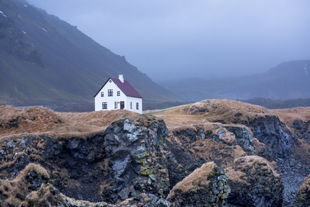 A small white building located in a remote seaside location is framed by gloomy fog and clouds during dusk.