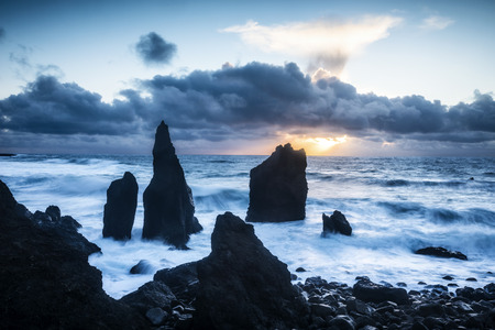 protruding:   A remote beach in Iceland shows sharp rocky reefs protruding 20 feet out of the shallow water during a sunset.