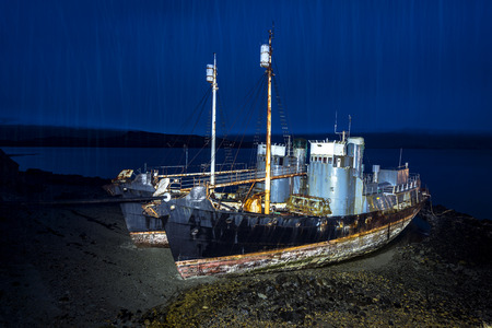 whaling:   Two abandoned whaling ships rest on a remote beach after Iceland scrapped their whaling program. Ships are light painted at night with heavy rain pouring through the blue light.