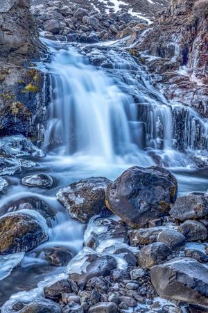 ciclos: Una cascada en Islandia cascadas por la ladera de una montaña escarpada en una piscina natural Foto de archivo