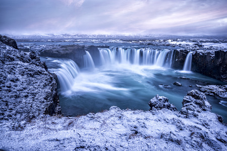 Godafoss Falls during Sunrise shows the water pouring over the edge and kicking up a misty cloud over the water with snow covering the cliffs.