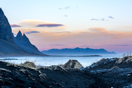 A volcanic sand beach in Iceland framed against jagged mountains and a beautiful pastel sunset as day slips into night.    Stock Photo