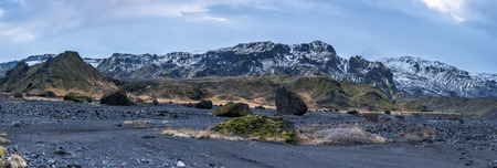 mountaintops:   An Iceland mountain range panorama shows the snow-covered mountaintops with dry volcanic landscape and arctic vegetation surrounding the terrain.