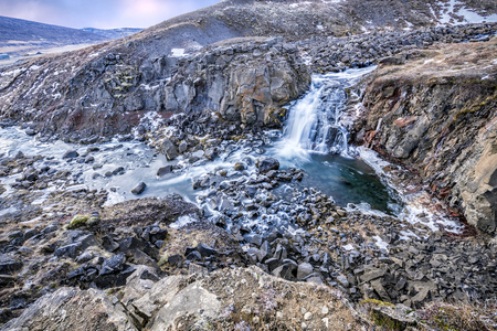 unaffected:   A waterfall in Iceland cascades down the side of a rugged mountain into a natural pool