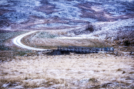 mingled:   A bridge in the middle of remote countryside in Iceland during winter shows the grassy terrain mingled with ice and snow.