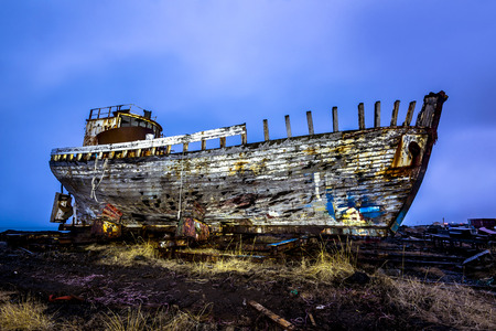 An old abandoned whaling ship from the early 1900s rests on a remote shipyard beach as it rots, exposing the ships wooden ribs and hull infrastructure. Image was shot at night and light painted.