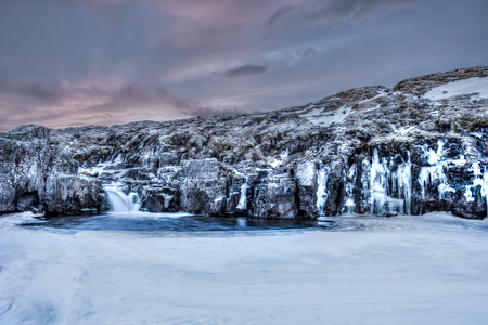 dark skies:  A frozen river in the highlands of Iceland framed by dark pastel skies and rugged terrain offers scenic landscape epitomizing the frozen wilderness.