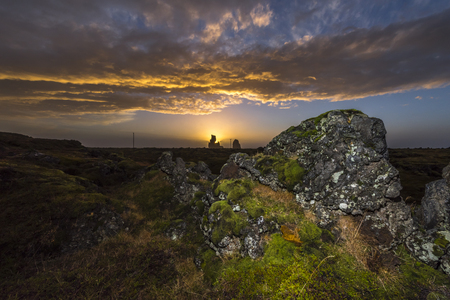 Sunset over an oceanfront marsh shows a very moody, dark landscape framed by rocks and vegetation