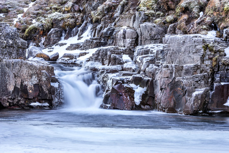 A waterfall surrounded by ice and snow in the highlands of Iceland framed rugged terrain offers scenic landscape epitomizing the frozen wilderness.