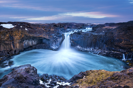 Aldeyjarfoss Falls at Sunrise shows the water pouring over the edge and kicking up a misty cloud over the water.