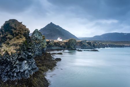 A small white building located in a remote seaside location is framed by gloomy fog and clouds during dusk.   Stock Photo