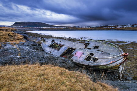 corrosion:   An old abandoned fishing vessel from the early 1900s rests on a remote beach as it rots, exposing the ships wooden ribs and hull infrastructure.    Stock Photo