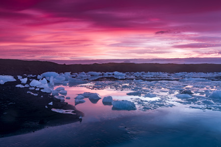 shorelines:   Icebergs in Jokulsarlon glacial lagoon during a vibrant red sunrise rests motionless as it is framed by cold ocean water.